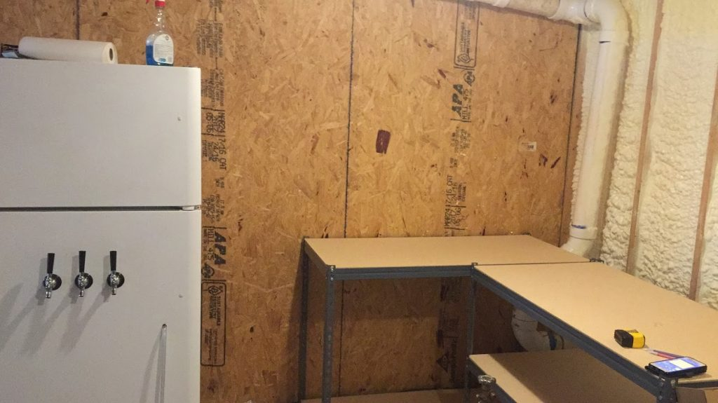 Empty worktable with a kegerator and unfinished walls. An empty brew room waiting for the electric brewing system to be built.